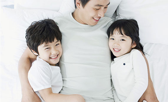 Picture of a smiling man  holding a daughter and son.